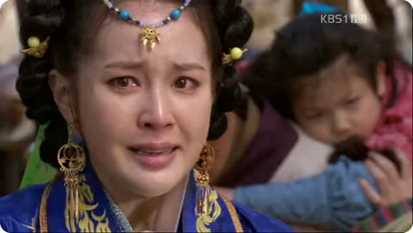 Princess Damju holding a dagger to her neck with her son behind her